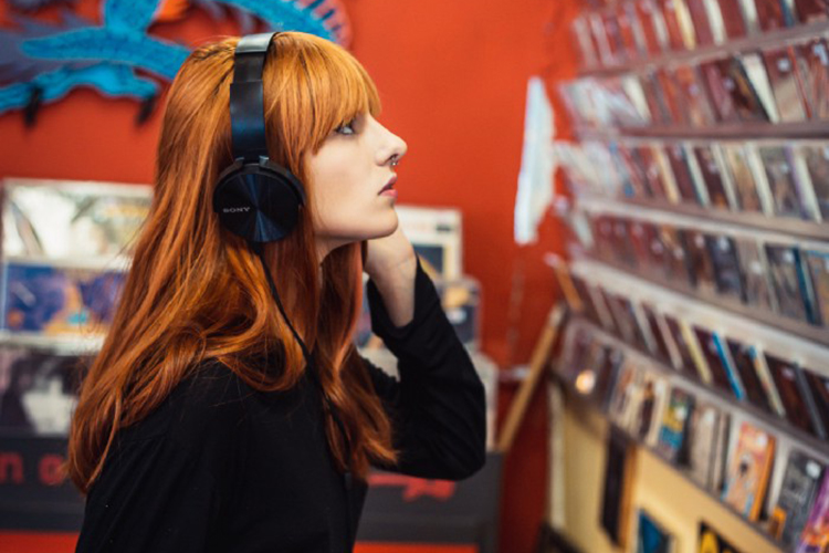 Woman at a record store listening to music through headphones